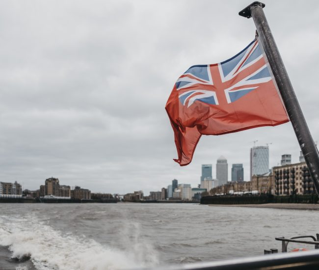 British Naval Flag on Thames Clippers boat on River Thames, Canary Wharf, London, UK.